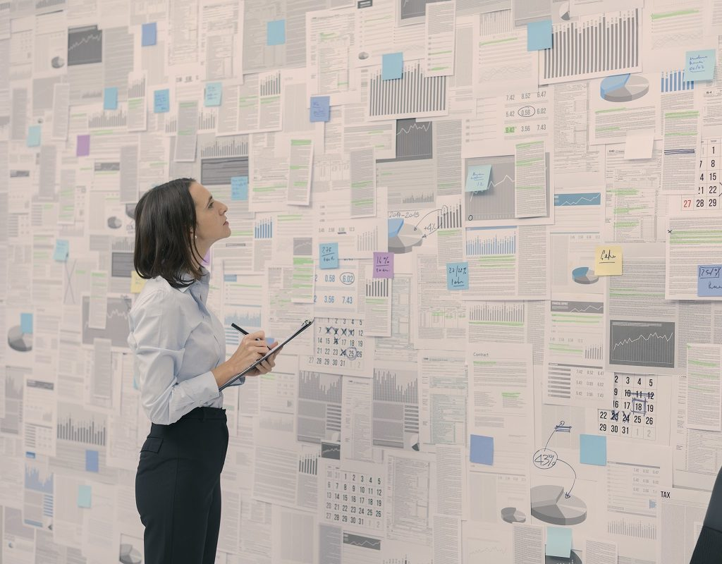 Corporate businesswoman checking financial data and reports hanging on a wall, management and strategy concept