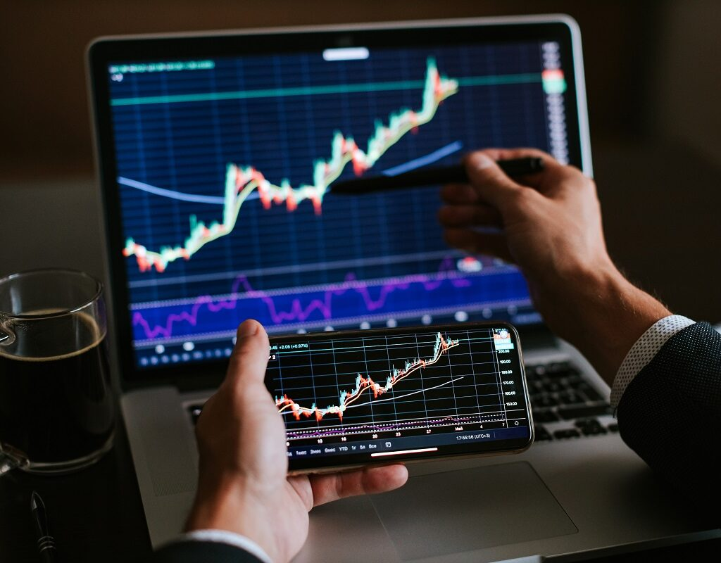 investment stockbroker risk analysis. Financial analysis using phone app and laptop. Market trading profit.